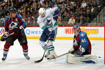 DENVER, CO - JANUARY 18:  Ryan Kesler #17 of the Vancouver Canucks tips the puck past goalie Craig Anderson #41 of the Colorado Avalanche for a second period goal as Adam Foote #52 of the Avalanche helps on defense at the Pepsi Center on January 18, 2011