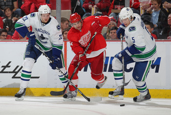 DETROIT, MI - DECEMBER 22:  Patrick Eaves #17 of the Detroit Red Wings chases after a puck between Alexander Edler #23 and Christian Ehrhoff #5 of the Vancouver Canucks in a game on December 22, 2010 at the Joe Louis Arena in Detroit, Michigan. The Wings