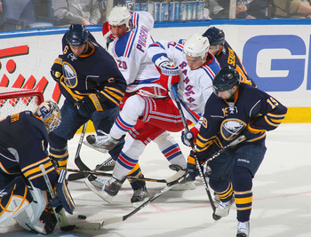 BUFFALO, NY - MARCH 30: Artem Anisimov #42 of the New York Rangers is knocked off his feet by Mike Weber #6 of the Buffalo Sabres  at HSBC Arena on March 30, 2011 in Buffalo, New York.  (Photo by Rick Stewart/Getty Images)