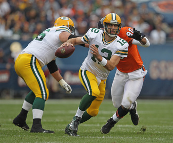 CHICAGO, IL - SEPTEMBER 25: Aaron Rodgers #12 of the Green Bay Packers moves out of the pocket under pressure from Julius Peppers #90 of the Chicago Bears at Soldier Field on September 25, 2011 in Chicago, Illinois. (Photo by Jonathan Daniel/Getty Images)