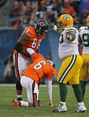 CHICAGO, IL - SEPTEMBER 25: Jay Cutler #6 of the Chicago Bears is helped up by Frank Omiyale #68 as B.J. Raji #90 of the Green Bay Packers celebrates at Soldier Field on September 25, 2011 in Chicago, Illinois. The Packers defeated the Bears 27-17. (Photo