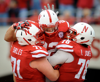 LINCOLN, NE - SEPTEMBER 17: Rex Burkhead #22 of the Nebraska Cornhuskers celebrates a touchdown with offensive linemen Jeremiah Sirles #71 and Marcel Jones #78 during their game at Memorial Stadium September 17, 2011 in Lincoln, Nebraska. Nebraska won 51-