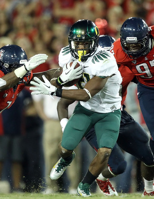 TUCSON, AZ - SEPTEMBER 24:  Runningback LaMichael James #21 of the Oregon Ducks rushes the football past Robert Golden #1 and Mohammed Usman #97 of the Arizona Wildcats during the second quarter of the college football game at Arizona Stadium on September