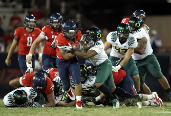 TUCSON, AZ - SEPTEMBER 24:  Runningback Keola Antolin #2 of the Arizona Wildcats rushes the football against Eddie Pleasant #11 of the Oregon Ducks during the third quarter of the college football game at Arizona Stadium on September 24, 2011 in Tucson, A