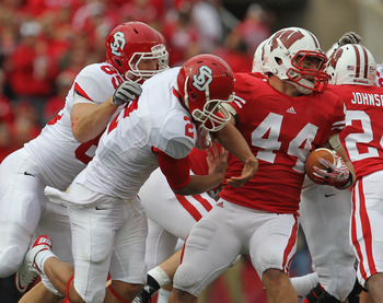 MADISON, WI - SEPTEMBER 24: Chris Borland #44 of the Wisconsin Badgers breaks away from Dante Warren #2 and Michael Neilson #85 of the South Dakota Coyotes after intercepting a pass at Camp Randall Stadium on September 24, 2011 in Madison Wisconsin. (Phot
