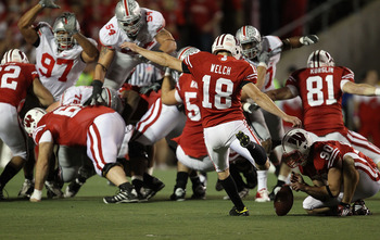 MADISON, WI - OCTOBER 16: Phillip Welch #18 of the Wisconsin Badgers kicks a field goal out of the hold of Ryan Wickesberg #90 against the Ohio State Buckeyes at Camp Randall Stadium on October 16, 2010 in Madison, Wisconsin. Wisconsin defeated Ohio State