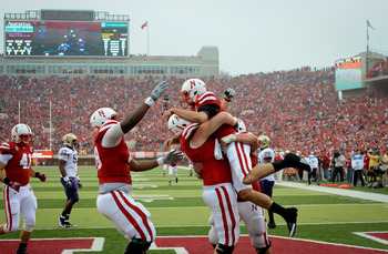LINCOLN, NE - SEPTEMBER 17: Taylor Martinez #3 of the Nebraska Cornhuskers celebrates a touchdown with teammates in a game against the Washington Huskies at Memorial Stadium September 17, 2011 in Lincoln, Nebraska. Nebraska won 51-38.(Photo by Eric Franci