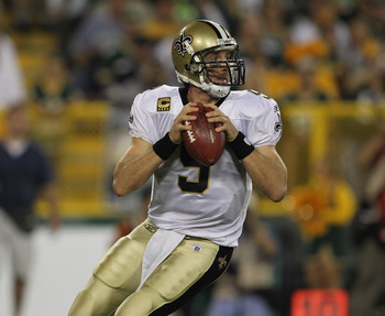 GREEN BAY, WI - SEPTEMBER 08:  Drew Brees #9 of the New Orleans Saints looks for a receiver against the Green Bay Packers during the NFL opening season game at Lambeau Field on September 8, 2011 in Green Bay, Wisconsin. The Packers defeated the Saints 42-