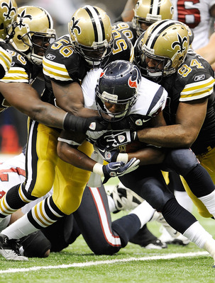 NEW ORLEANS, LA - SEPTEMBER 25:  Cameron Jordan #94 and Jo-Lonn Dunbar #56 of the New Orleans Saints bring down Ben Tate #44 of the Houston Texans during a game being held at the Louisiana Superdome on September 25, 2011 in New Orleans, Louisiana.  The Sa