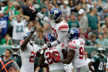 PHILADELPHIA, PA - SEPTEMBER 25: Defensive back  Aaron Ross #31 of the New York Giants celebrates with teammates  Antrel Rolle #26, Kenny Phillips #21 and  Mathias Kiwanuka #93 after Ross intercepted a Philadelphia Eagles pass in the fourth quarter at Lin