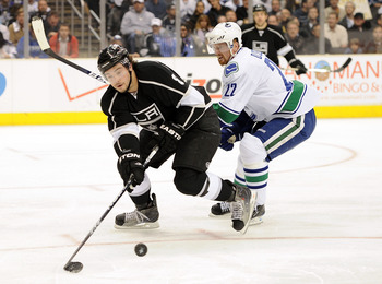 LOS ANGELES, CA - APRIL 21:  Drew Doughty #8 of the Los Angeles Kings clears the puck in front of Daniel Sedin #22 of the Vancouver Canucks during the first period in game four of the Western Conference Quarter-final at Staples Center on April 21, 2010 in