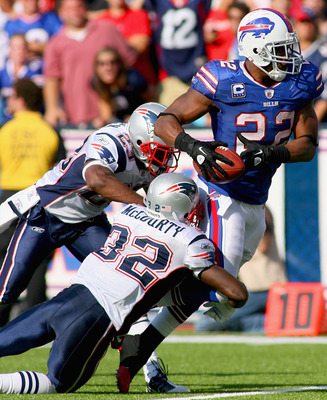 ORCHARD PARK, NY - SEPTEMBER 25:  Fred Jackson #22 of the Buffalo Bills runs against  Leigh Bodden #23 and  Devin McCourty #32 of the New England Patriots at Ralph Wilson Stadium on September 25, 2011 in Orchard Park, New York. Buffalo won 34-31.  (Photo