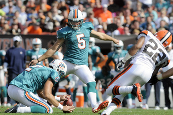 CLEVELAND, OH - SEPTEMBER 25: Punter Brandon Fields #2 holds for place kicker Dan Carpenter #5 of the Miami Dolphins as he kicks a 38 yard field goal during the fourth quarter against the Cleveland Browns at Cleveland Browns Stadium on September 25, 2011