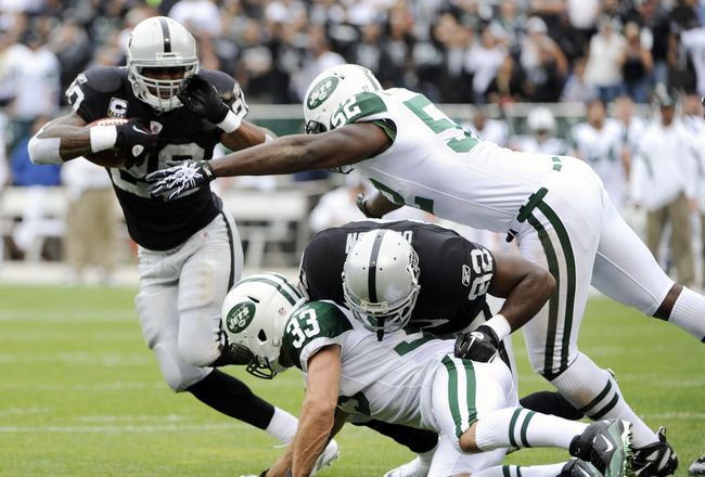 OAKLAND, CA - SEPTEMBER 25: Darren McFadden #20 of the Oakland Raiders pushes away from David Harris #52 and Eric Smith #33 of the New York Jets for a two yard touchdown run in the first quarter during an NFL football game at the O.co Coliseum September 2