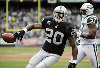 OAKLAND, CA - SEPTEMBER 25: Darren McFadden #20 of the Oakland Raiders tosses the ball away after scoring on a two yard touchdown run against the New York Jets in the first quarter during an NFL football game at the O.co Coliseum September 25, 2011 in Oak