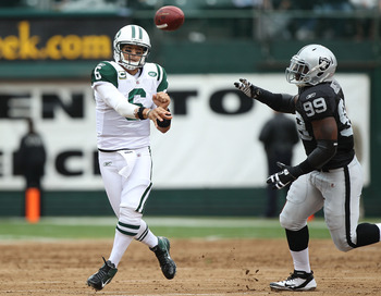 OAKLAND, CA - SEPTEMBER 25:  Mark Sanchez #6 of the New York Jets passes  against Lamarr Houston #99 of the Oakland Raiders at O.co Coliseum on September 25, 2011 in Oakland, California.  (Photo by Jed Jacobsohn/Getty Images)