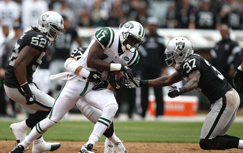 OAKLAND, CA - SEPTEMBER 25:  Plaxico Burress #17 of the New York Jets catches a passs against Matt Giordano #27 and Chris Johnson #37 of the Oakland Raiders and at O.co Coliseum on September 25, 2011 in Oakland, California.  (Photo by Jed Jacobsohn/Getty