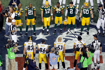 ARLINGTON, TX - FEBRUARY 06:  The captains, Jarrett Bush #24, Charles Woodson #21, Aaron Rodgers #12, Greg Jennings #85, Mason Crosby #2 and A.J. Hawk #50 of the Green Bay Packers and Heath Miller #83, Hines Ward #86, James Farrior #51 and Keyaron Fox #57