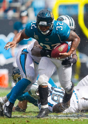 CHARLOTTE, NC - SEPTEMBER 25: Running back Maurice Jones-Drew #32 of the Jacksonville Jaguars tries to escape the grasp of a Carolina Panthers defender during third quarter action at Bank of America Stadium on September 25, 2011 in Charlotte, North Caroli