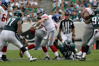 PHILADELPHIA, PA - SEPTEMBER 25:  Quarterback  Eli Manning #10 of the New York Giants throws a pass while being pressured by Phillip Hunt #76 of the Philadelphia Eagles during the first half at Lincoln Financial Field on September 25, 2011 in Philadelphia