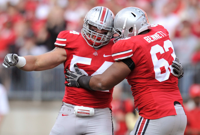 COLUMBUS, OH - SEPTEMBER 24:  John Simon #54 of the Ohio State Buckeyes and Michael Bennett #63 of the Ohio State Buckeyes celebrate over quarterback Tyler Hansen #9 of the Colorado Buffaloes after Simon pressured Hansen to throw an incompletion at Ohio S