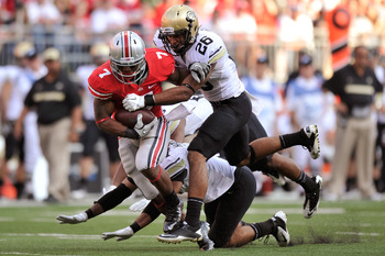 COLUMBUS, OH - SEPTEMBER 24:  Ray Polk #26 of the Colorado Buffaloes brings down Jordan Hall #7 of the Ohio State Buckeyes after a big gain in the first half at Ohio Stadium on September 24, 2011 in Columbus, Ohio. Ohio State defeated Colorado 37-17.  (Ph