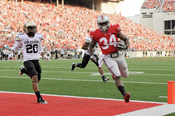 COLUMBUS, OH - SEPTEMBER 24:  Carlos Hyde #34 of the Ohio State Buckeyes scores on a five-yard touchdown run in the second half as Greg Henderson #20 of the Colorado Buffaloes chases at Ohio Stadium on September 24, 2011 in Columbus, Ohio. Ohio State defe
