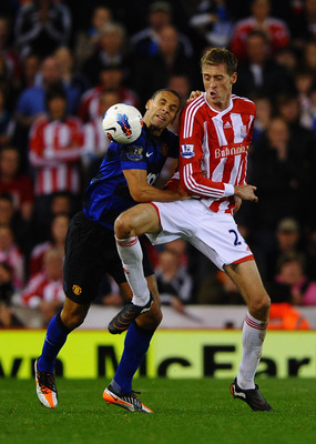 STOKE ON TRENT, ENGLAND - SEPTEMBER 24:  Rio Ferdinand of Manchester United and Peter Crouch of Stoke City battle for the ball during the Barclays Premier League match between Stoke City and Manchester United at the Britannia Stadium on September 24, 2011