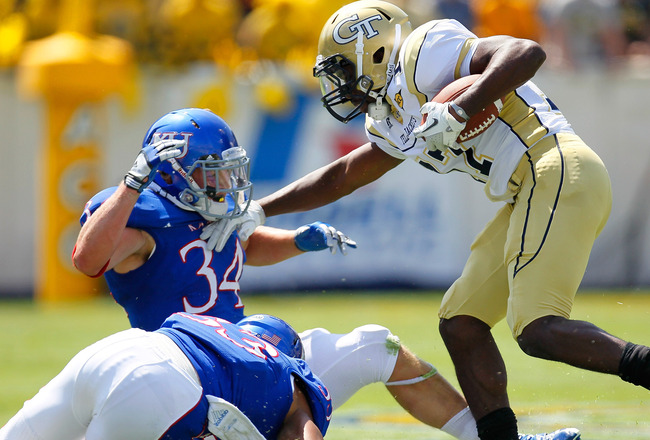 ATLANTA, GA - SEPTEMBER 17:  Orwin Smith #17 of the Georgia Tech Yellow Jackets stiff arms Huldon Tharp #34 of the Kansas Jayhawks at Bobby Dodd Stadium on September 17, 2011 in Atlanta, Georgia.  (Photo by Kevin C. Cox/Getty Images)