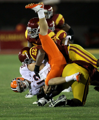 LOS ANGELES, CA - SEPTEMBER 17:  Quarterback Ryan Nassib #12 of the Syracuse Orangemen is tackled after running for a first down by defensive end Devon Kennard #42 and linebacker Lamar Dawson #55 of the USC Trojans at the Los Angeles Memorial Coliseum on