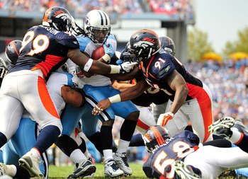NASHVILLE, TN - SEPTEMBER 25: Chris Johnson #28 of the Tennessee Titans is stopped by the Denver Broncos defense at LP Field on September 25, 2011 in Nashville, Tennessee. Tennessee won 17-14. (Photo by Grant Halverson/Getty Images)