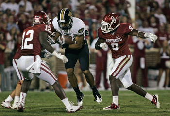 NORMAN, OK - SEPTEMBER 24:  Quarterback James Franklin #1 of the Missouri Tigers tries to rush past defensive back Lynn Gabe #9  of the Oklahoma Sooners during the second half September 24, 2011 at Gaylord Family-Oklahoma Memorial Stadium in Norman, Oklah