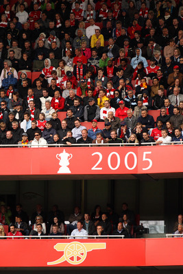 LONDON, ENGLAND - MAY 15:  Arsenal fans watch the action from their seats behind a sign displaying the last trophy that the club won in 2005 during the Barclays Premier League match between Arsenal and Aston Villa at the Emirates Stadium on May 15, 2011 i