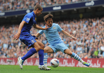 MANCHESTER, ENGLAND - SEPTEMBER 24:  David Silva of Manchester City is challenged by Jack Rodwell of Everton during the Barclays Premier League match between Manchester City and Everton at the Etihad Stadium on September 24, 2011 in Manchester, England.