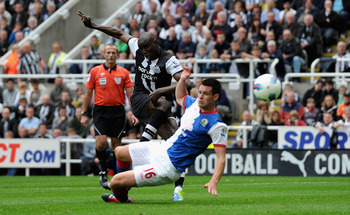 NEWCASTLE UPON TYNE, ENGLAND - SEPTEMBER 24:  Demba Ba of Newcastle scores his team's opening goal past Scott Dann of Blackburn during the Barclays Premier League match between Newcastle United and Blackburn Rovers at St James' Park on September 24, 2011