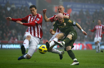 STOKE ON TRENT, ENGLAND - DECEMBER 28: Andrew Johnson of Fulham is tackled by Andy Wilkinson and Robert Huth of Stoke City during the Barclays Premier League match between Stoke City and Fulham at Britannia Stadium on December 28, 2010 in Stoke on Trent,