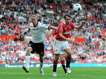 MANCHESTER, ENGLAND - APRIL 09: Michael Owen of Manchester United wins a header against Brede Hangeland of Fulham during the Barclays Premier League match between Manchester United and Fulham at Old Trafford on April 9, 2011 in Manchester, England.  (Phot