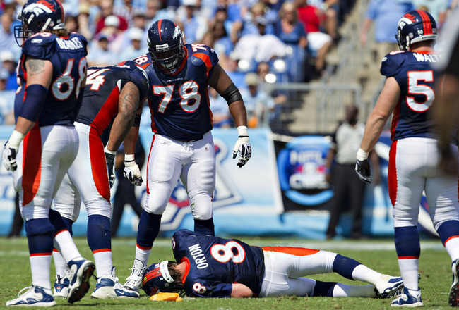 NASHVILLE, TN - SEPTEMBER 25:  Kyle Orton #8 of the Denver Broncos lays on the ground by a penalty flag after being hit during a game against the Tennessee Titans at LP Field on September 25, 2011 in Nashville, Tennessee.   The Titans defeated the Broncos