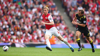 LONDON, ENGLAND - SEPTEMBER 24:  Per Mertesacker of Arsenal escapes a challenge from Kevin Davies of Bolton Wanderers during the Barclays Premier League match between Arsenal and Bolton Wanderers at Emirates Stadium on September 24, 2011 in London, Englan