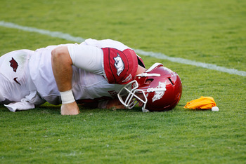 TUSCALOOSA, AL - SEPTEMBER 24:  Tyler Wilson #8 of the Arkansas Razorbacks holds his helmet after he was hit late by Quinton Dial #90 of the Alabama Crimson Tide lat Bryant-Denny Stadium on September 24, 2011 in Tuscaloosa, Alabama.  (Photo by Kevin C. Co