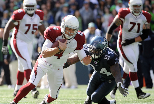 SEATTLE, WA - SEPTEMBER 25:   Kevin Kolb #4 of the Arizona Cardinals dives for a first down as he is chased by  Anthony Hargrove #94 of the Seattle Seahawks during the first quarter at CenturyLink Field on September 25, 2011 in Seattle, Washington.  (Phot