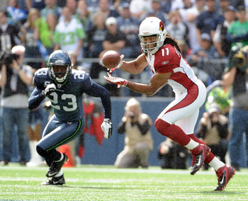 SEATTLE, WA - SEPTEMBER 25:   Larry Fitzgerald #11 of the Arizona Cardinals makes a catch in front of  Marcus Trufant #23 of the Seattle Seahawks during the first quarter at CenturyLink Field on September 25, 2011 in Seattle, Washington.  (Photo by Harry