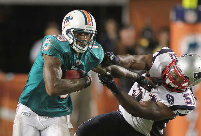 MIAMI GARDENS, FL - SEPTEMBER 12: Reciever Brandon Marshall#19 of the Miami Dolphins stiff arms Linebacker Dane Fletcher #51 of the New England Patriots at Sun Life Stadium on September 12, 2011 in Miami Gardens, Florida.  (Photo by Marc Serota/Getty Imag