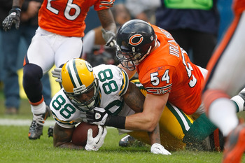 CHICAGO, IL - SEPTEMBER 25: Greg Jennings #85 of the Green Bay Packers dives for additional yardage as he is tackled by Brian Urlacher #54 the Chicago Bears at Soldier Field on September 25, 2011 in Chicago, Illinois. (Photo by Scott Boehm/Getty Images)