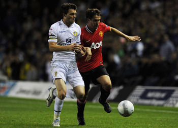 LEEDS, ENGLAND - SEPTEMBER 20:  Michael Owen (R) of Manchester United is tackled by Jonathan Howson of Leeds during the Carling Cup Third Round match between Leeds United and Manchester United at Elland Road on September 20, 2011 in Leeds, England.  (Phot