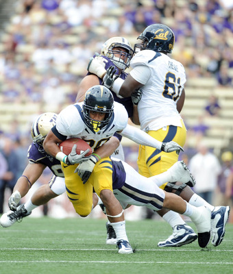 SEATTLE, WA - SEPTEMBER 24:  Isi Sofele #20 of the California Golden Bears runs as he is tackled by Everrette Thompson #92 of the Washington Huskies at Husky Stadium on September 24, 2011 in Seattle, Washington.  (Photo by Harry How/Getty Images)