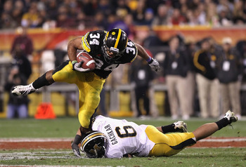 TEMPE, AZ - DECEMBER 28:  Runningback Marcus Coker #34 of the Iowa Hawkeyes rushes the football over Andrew Gachkar #6 of the Missouri Tigers during the Insight Bowl at Sun Devil Stadium on December 28, 2010 in Tempe, Arizona.  The Hawkeyes defeated the T