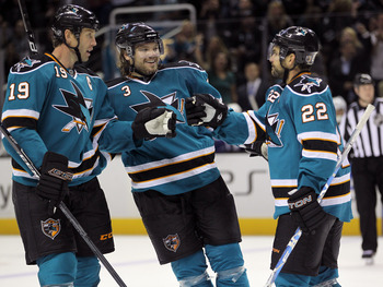 SAN JOSE, CA - SEPTEMBER 29:  Dan Boyle #22 of the San Jose Sharks is congratulated by Douglas Murray #3 and Joe Thornton #19 after he scored a goal against the Vancouver Canucks at HP Pavilion on September 29, 2011 in San Jose, California.  (Photo by Ezr