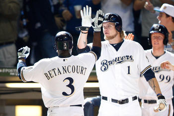 MILWAUKEE, WI - OCTOBER 01:  Yuniesky Betancourt #3 of the Milwaukee Brewers is congratulated by teammate Corey Hart #1 after scoring against the Arizona Diamondbacks in the 6th inning during Game One of the National League Division Series at Miller Park