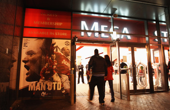 MANCHESTER, ENGLAND - OCTOBER 20:  Manchester United fans walk past a Wayne Rooney display at the megastore prior to the UEFA Champions League Group C match between Manchester United and Bursaspor Kulubu at Old Trafford on October 20, 2010 in Manchester,